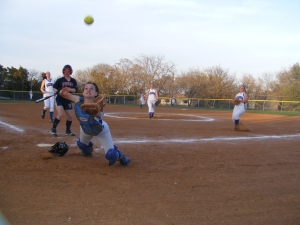 Nolan Catholic High Lady Vikings catcher Martha Thomas zeroes the apparent acceleration of a pop-up